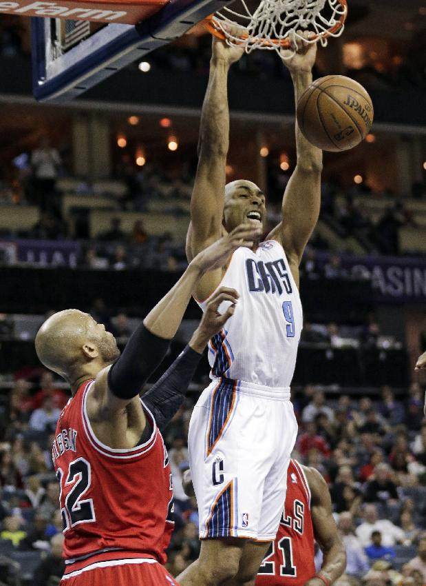 Charlotte Bobcats' Gerald Henderson (9) dunks on Chicago Bulls' Taj Gibson during the first half of an NBA basketball game in Charlotte, N.C., Saturday, Jan. 25, 2014