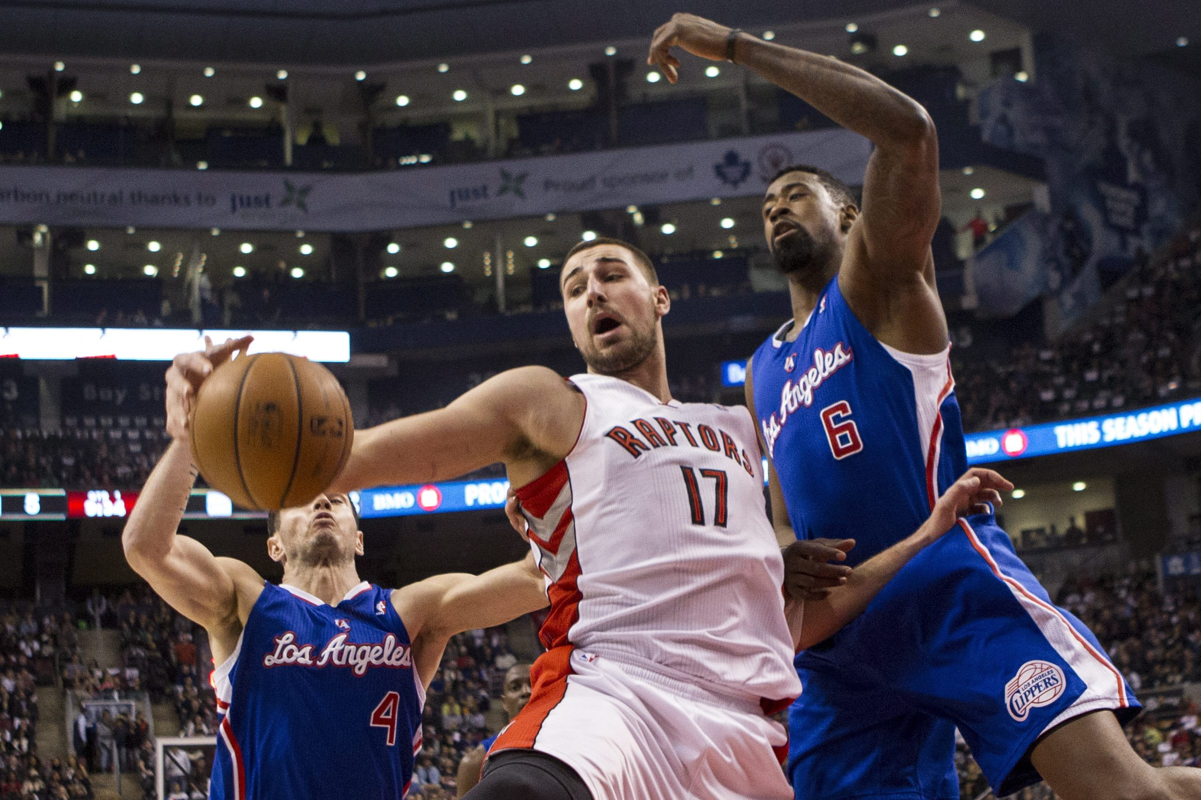 Toronto Raptors' Jonas Valanciunas, center, fights for a loose ball with Los Angeles Clippers DeAndre Jordan, right, and J.J. Redick during the first half of an NBA basketball game, Saturday, Jan. 25, 2014 in Toronto