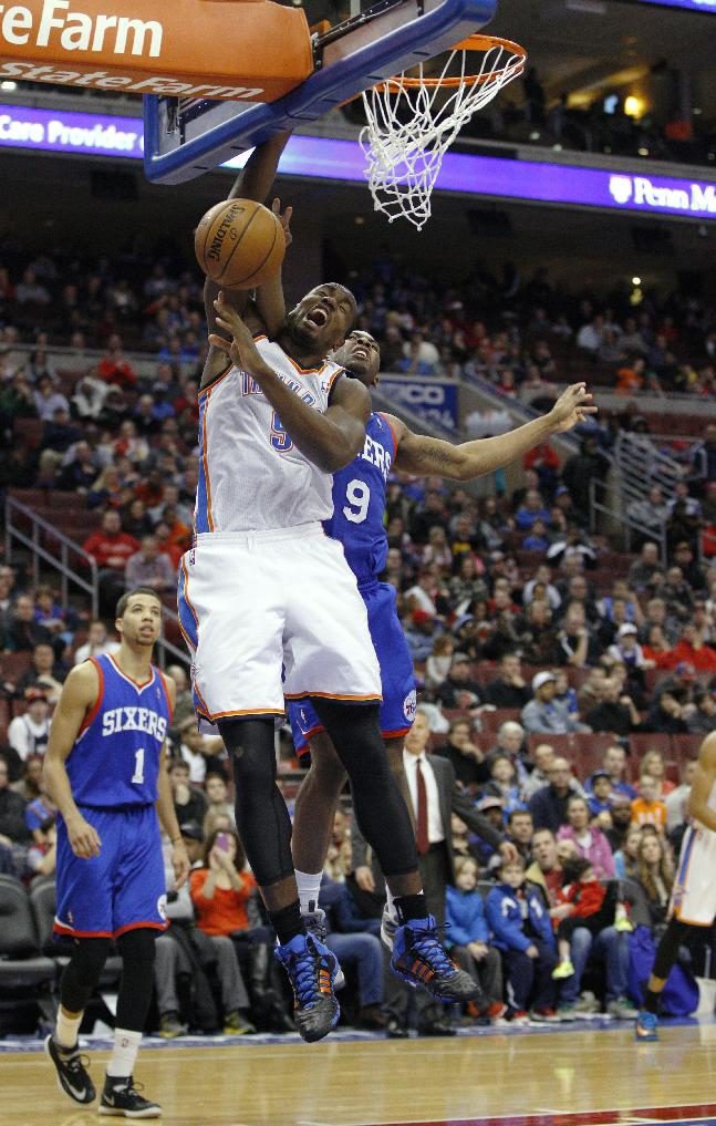 Oklahoma City Thunder's Serge Ibaka, left, is fouled on a shot attempt, by Philadelphia 76ers' James Anderson, right, during the second half of an NBA basketball game, Saturday, Jan. 25, 2014, in Philadelphia. The Thunder won 103-91