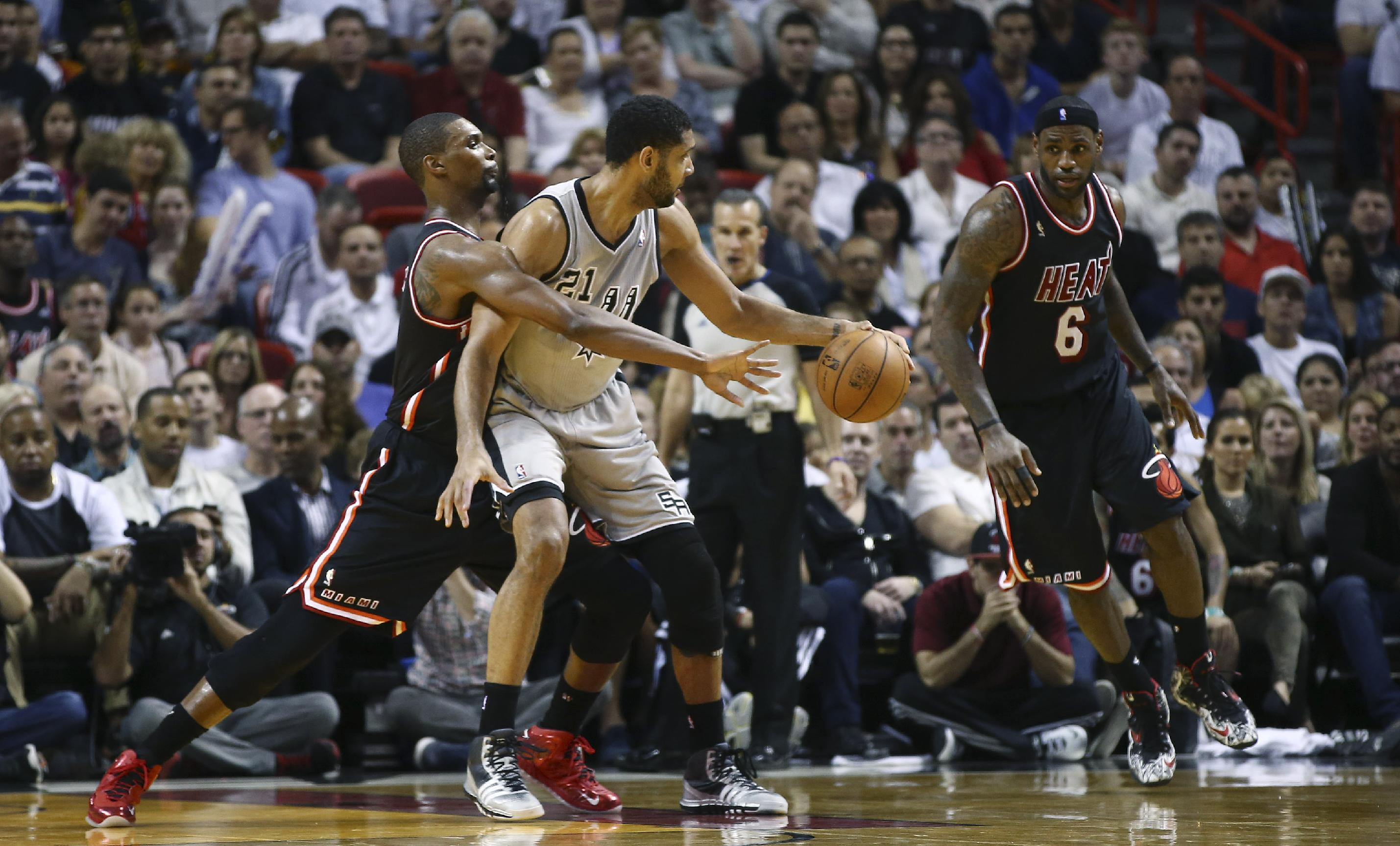 Miami Heat's Chris Bosh, (1) tries to steal the ball from San Antonio Spurs' Tim Duncan (21) as LeBron James (60 applies pressure during the second half of a NBA basketball game in Miami, Sunday, Jan. 26, 2014. The Heat won 113-101