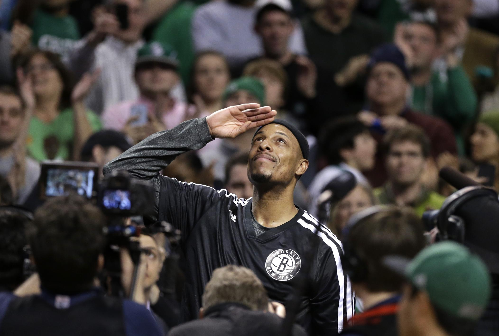 Brooklyn Nets forward Paul Pierce, center, formerly of the Boston Celtics, salutes the crowd during a tribute to him in the first half of an NBA basketball game against the Boston Celtics, Sunday, Jan. 26, 2014, in Boston