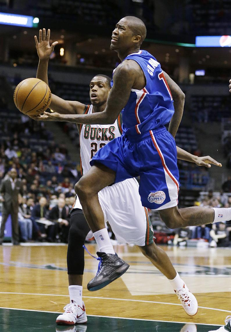Los Angeles Clippers' Jamal Crawford, right, drives to the basket against Milwaukee Bucks' Khris Middleton (22) during the first half of an NBA basketball game, Monday, Jan. 27, 2014, in Milwaukee