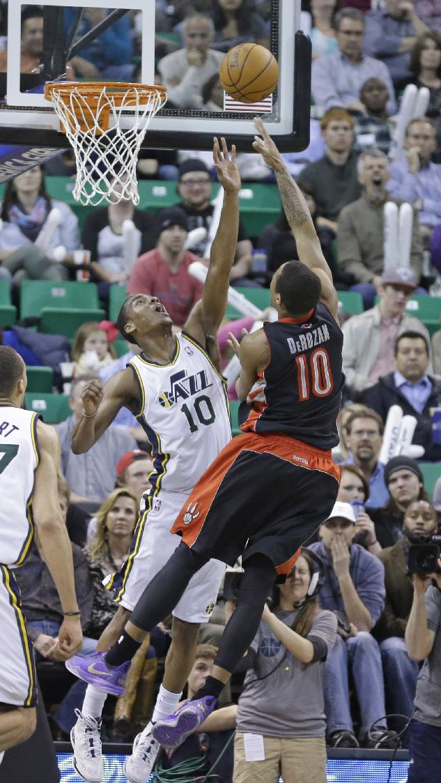 Toronto Raptors' DeMar DeRozan (10) shoots as Utah Jazz's Alec Burks (10) defends in the fourth quarter of an NBA basketball game, Monday, Feb. 3, 2014, in Salt Lake City. The Raptors won 94-79