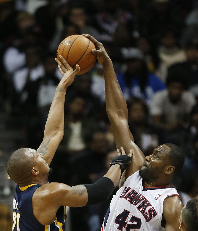 Indiana Pacers power forward David West (21) has his shot blocked by Atlanta Hawks power forward Elton Brand (42) in the second half of an NBA basketball game, Tuesday, Feb. 4, 2014, in Atlanta. Indiana won 89-85