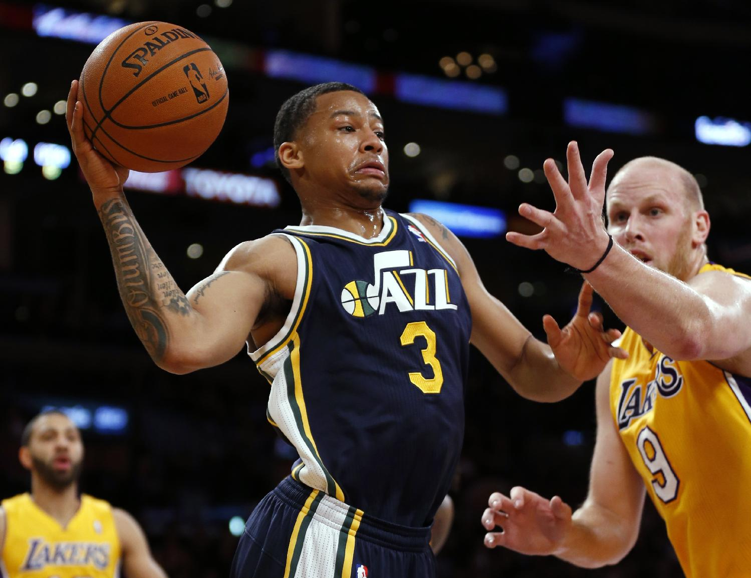Utah Jazz's Trey Burke, left, passes around Los Angeles Lakers' Chris Kaman during the first half of an NBA basketball game in Los Angeles, Tuesday, Feb. 11, 2014
