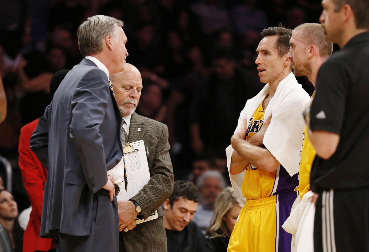 Los Angeles Lakers' Steve Nash, third from left, talks with coach Mike D'Antoni, left, as athletic trainer Gary Vitti, second from left, stands with them along with Steve Blake, right, while officials review a call at the end of the first half of an NBA basketball game against the Utah Jazz in Los Angeles, Tuesday, Feb. 11, 2014