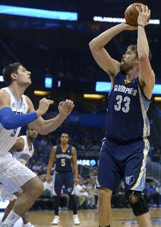 Memphis Grizzlies center Marc Gasol (33) goes up for a shot in front of Orlando Magic center Nikola Vucevic during the first half of an NBA basketball game in Orlando, Fla., Wednesday, Feb. 12, 2014