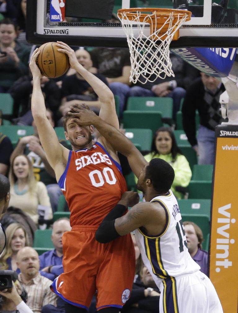 Philadelphia 76ers' Spencer Hawes (00) pulls down a rebound as Utah Jazz's Derrick Favors, right, defends in the first quarter of an NBA basketball game on Wednesday, Feb. 12, 2014, in Salt Lake City