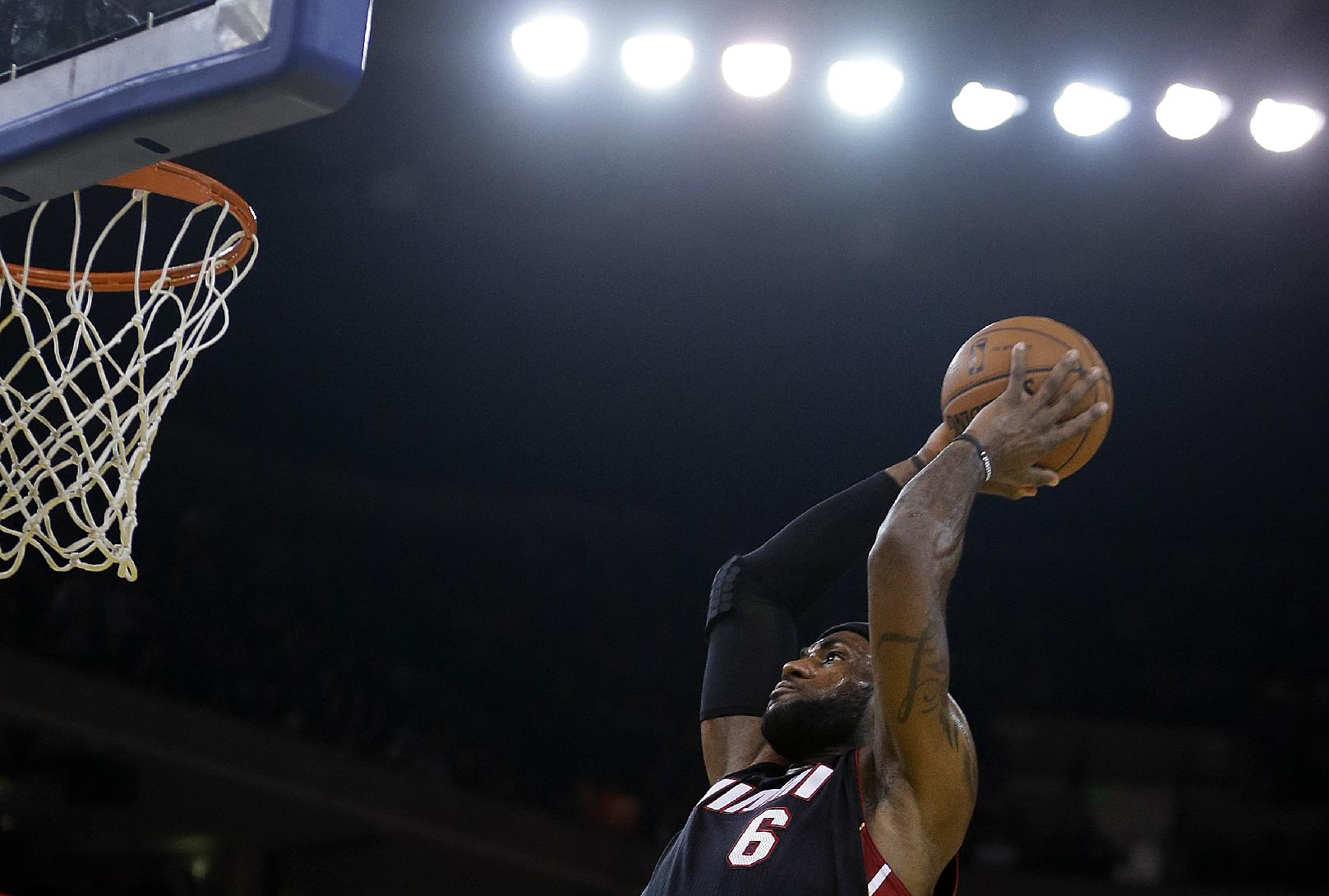 Miami Heat's LeBron James lays up a shot against the Golden State Warriors during the first half of an NBA basketball game on Wednesday, Feb. 12, 2014, in Oakland, Calif
