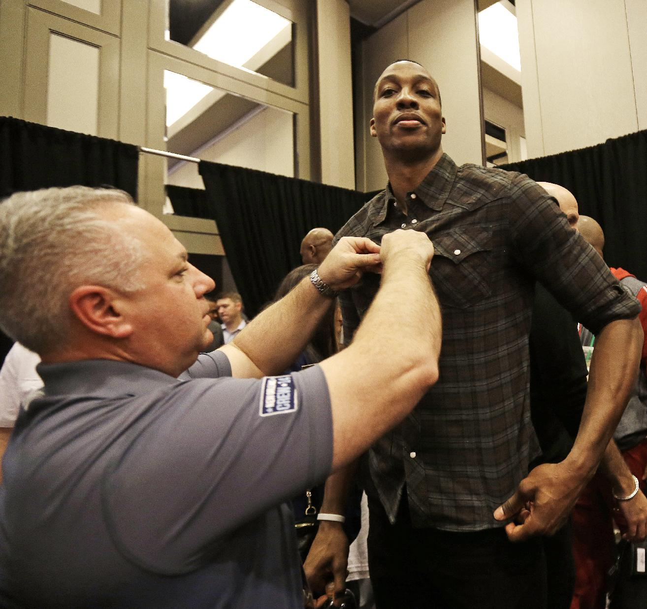CORRECTS ID TO HOUSTON ROCKETS' DWIGHT HOWARD, NOT OKLAHOMA CITY THUNDER KEVIN DURANT - Houston Rockets' Dwight Howard has a microphone installed during the NBA All Star basketball news conference, Friday, Feb. 14, 2014, in New Orleans