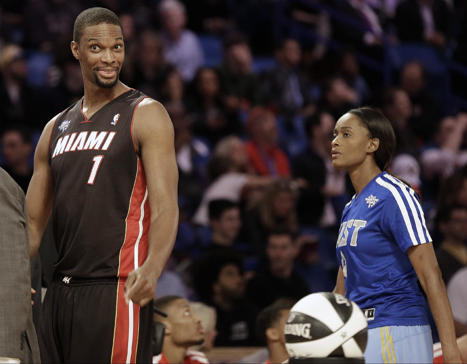 Chris Bosh, of the Miami Heat (1) and WNBA Chicago Sky player Elena Delle Donne walk the court during the skills competition at the NBA All Star basketball game, Saturday, Feb. 15, 2014, in New Orleans