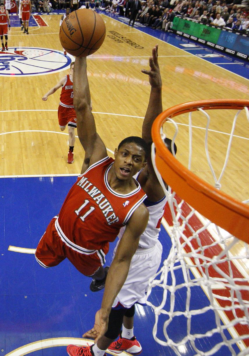Milwaukee Bucks' Brandon Knight (11) dunks past Philadelphia 76ers' Thaddeus Young during the first half of an NBA basketball game, Monday, Feb. 24, 2014, in Philadelphia