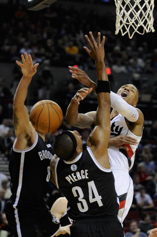 Portland Trail Blazers' Damian Lillard (0) is fouled shooting by Brooklyn Nets' Paul Pierce (34) during the second half of an NBA basketball game in Portland, Ore., Wednesday Feb. 26, 2014. The Trail Blazers beat the Nets 124-80
