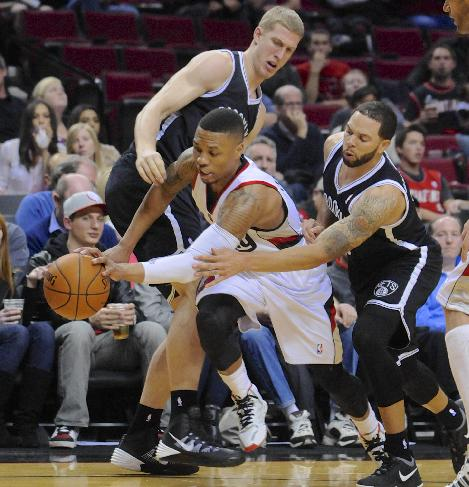 Portland Trail Blazers' Damian Lillard (0) drives against Brooklyn Nets' Alan Anderson, right, and Mason Plumlee (1) during the second half of an NBA basketball game in Portland, Ore., Wednesday Feb. 26, 2014. The Trail Blazers beat the Nets 124-80