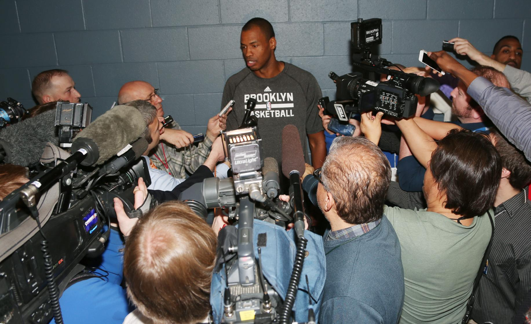 Brooklyn Nets center Jason Collins talks to reporters before the Nets faced the Denver Nuggets in an NBA basketball game in Denver on Thursday, Feb. 27, 2014