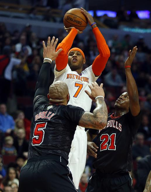 New York Knicks small forward Carmelo Anthony (7) shoots over Chicago Bulls forwards Carlos Boozer (5) and Jimmy Butler (21) during the first half of an NBA basketball game on Sunday, March 2, 2014, in Chicago