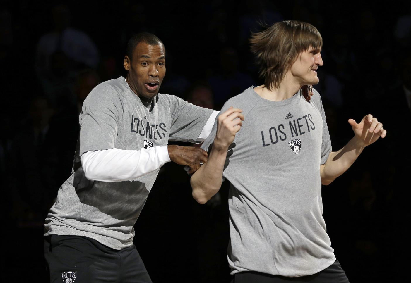Brooklyn Nets' Jason Collins, left, and Andrei Kirilenko join the huddle before the start of the NBA basketball game against the Chicago Bulls, Monday, March 3, 2014, in New York