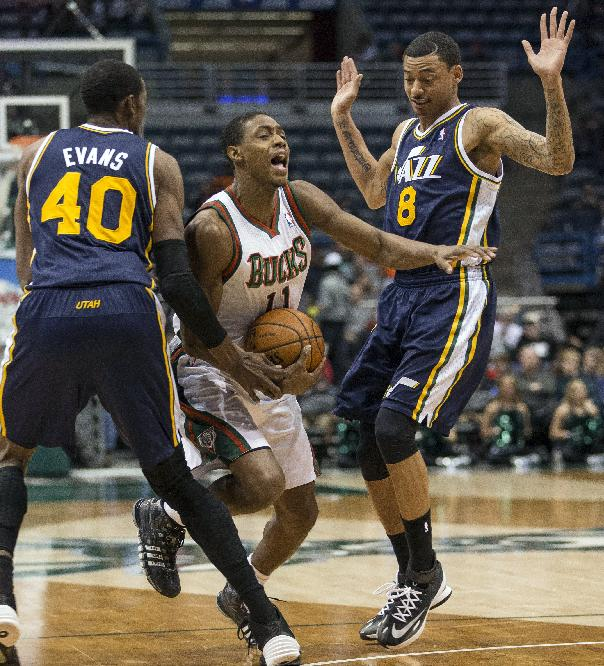 Milwaukee Bucks' Brandon Knight, center, is fouled by Utah Jazz Diante Garrett, right, with teammate Jeremy Evans, left, during the first half of an NBA basketball game Monday, March 3, 2014, in Milwaukee
