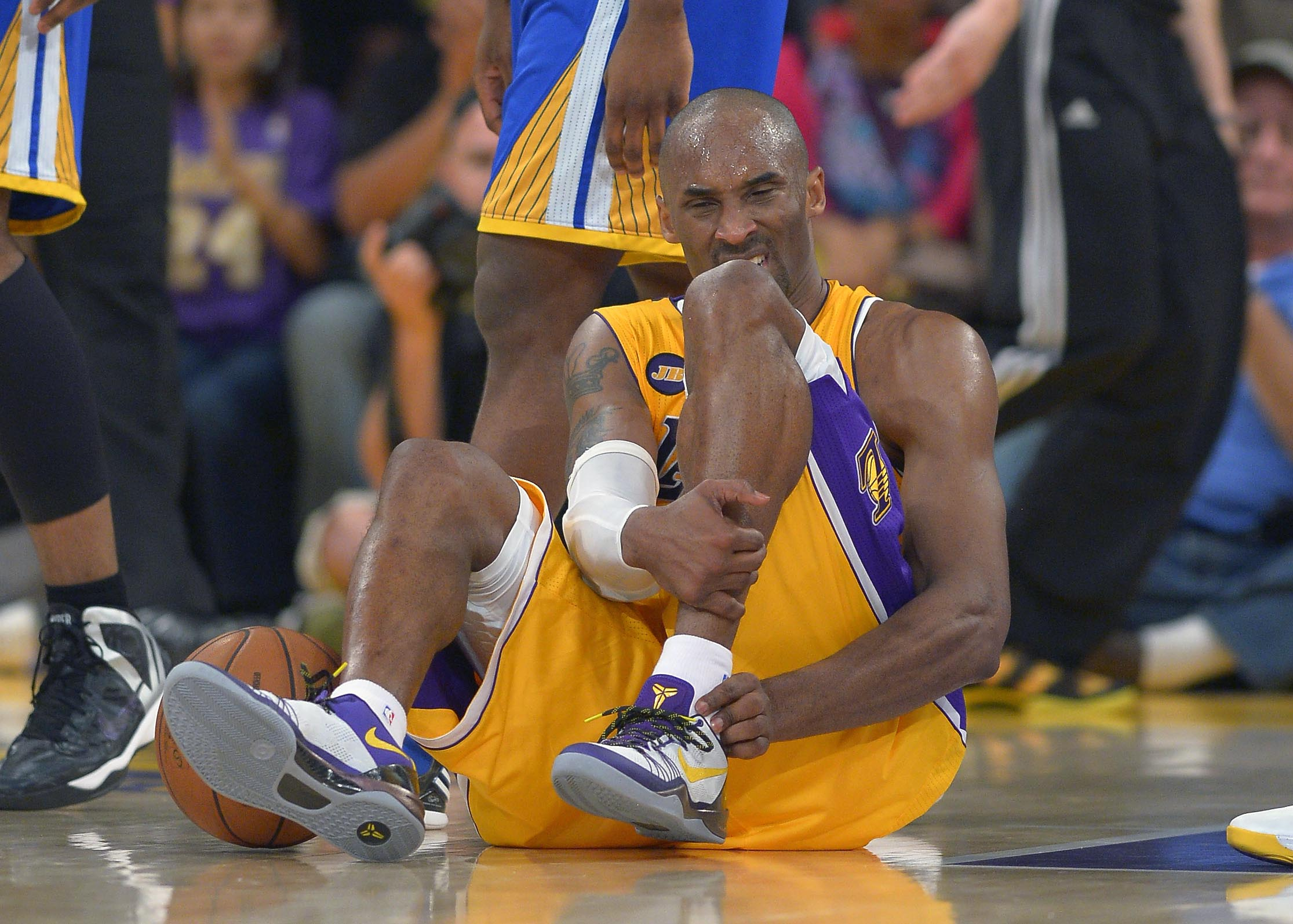 In this April 12, 2013 file photo, Los Angeles Lakers guard Kobe Bryant grimaces after being injured during the second half of their NBA basketball game against the Golden State Warriors, in Los Angeles. Bryant won't be back on the court for the Lakers this season. The Lakers said Bryant was examined by team physician Dr. Steve Lombardo, who determined that the left knee injury that has kept Bryant out of the lineup still hasn't healed