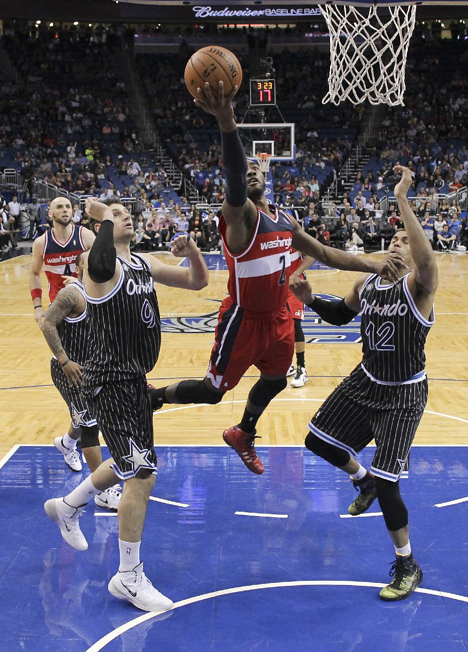 Washington Wizards' John Wall (2) drives in for a shot between Orlando Magic's Nikola Vucevic (9) and Tobias Harris (12) during the second half of an NBA basketball game in Orlando, Fla., Friday, March 14, 2014. Washington won in overtime, 105-101