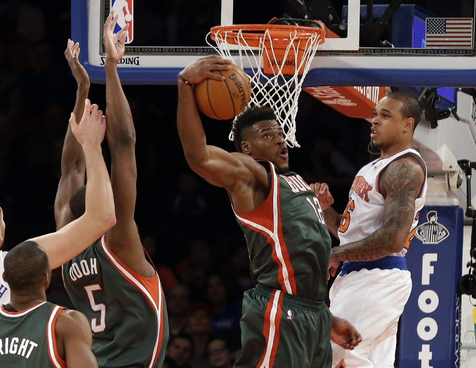 Milwaukee Bucks' Jeff Adrien, center, grabs a rebound of a shot by New York Knicks' Shannon Brown, right, in the fourth quarter of an NBA basketball game at New York's Madison Square Garden,  Saturday, March 15, 2014. The Knicks won 115-94