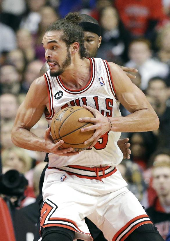 Chicago Bulls center Joakim Noah (13) works with the ball against Sacramento Kings forward Reggie Evans during the first half of an NBA basketball game in Chicago on Saturday, March. 15, 2014