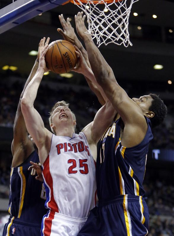 Detroit Pistons guard Kyle Singler (25) tries going to the basket against Indiana Pacers center Andrew Bynum, right, and guard Rasual Butler, left, during the second half of an NBA basketball game Saturday, March 15, 2014, in Detroit. The Pacers defeated the Pistons 1122-104 in overtime
