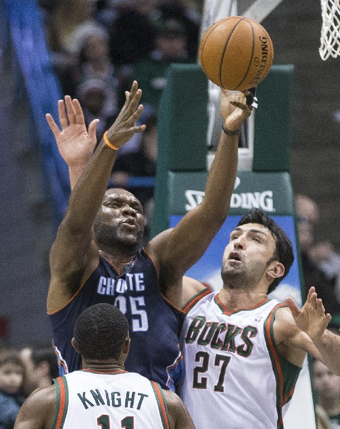 Milwaukee Bucks' Zaza Pachulia (27) and Brandon Knight defend against Charlotte Bobcats' Al Jefferson during the second half of an NBA basketball game on Sunday, March 16, 2014, in Milwaukee