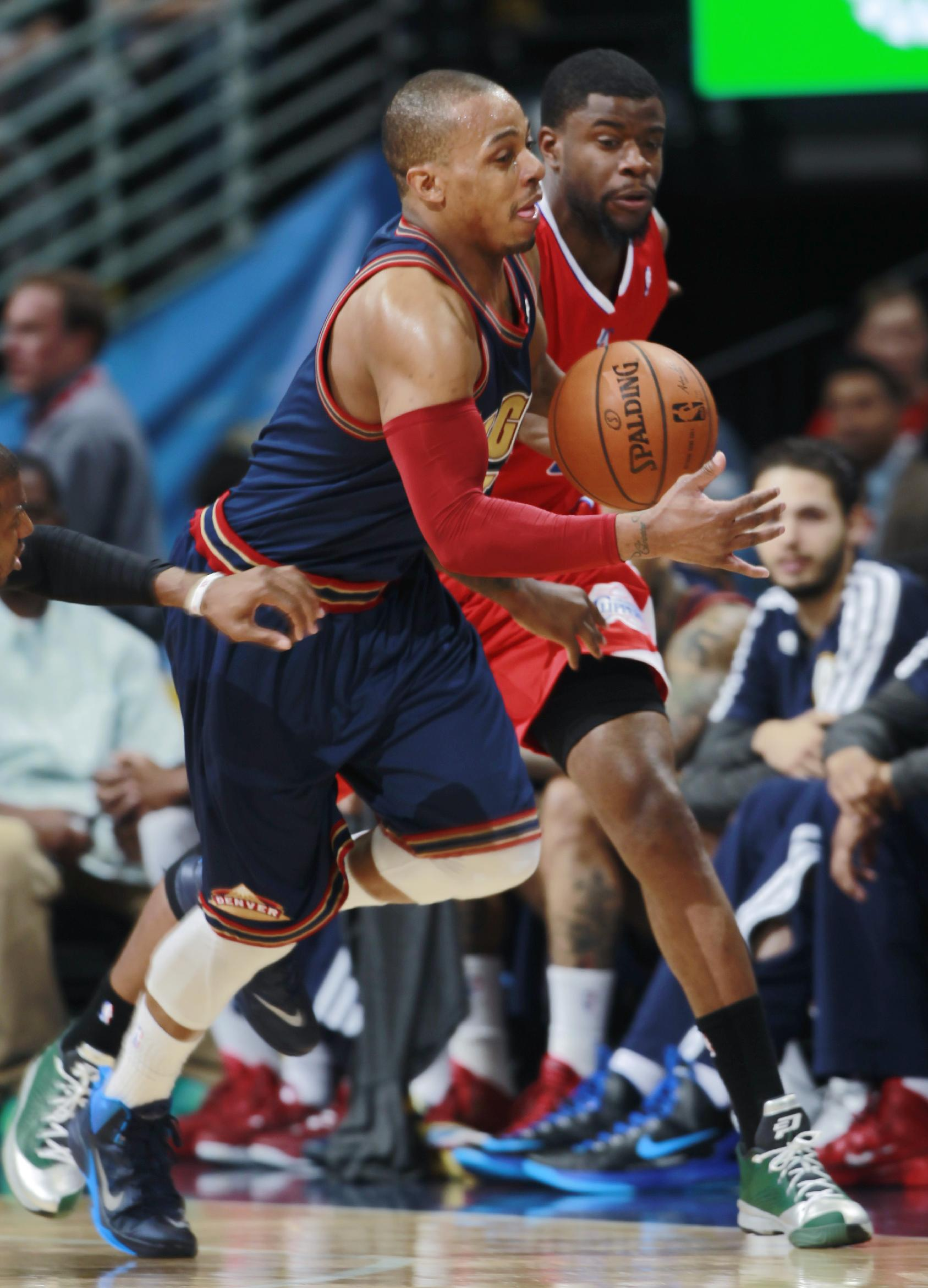 Denver Nuggets guard Randy Foye, front, picks up loose ball in front of Los Angeles Clippers guard Reggie Bullock in the third quarter of the Nuggets' 110-100 victory in an NBA basketball game in Denver on Monday, March 17, 2014