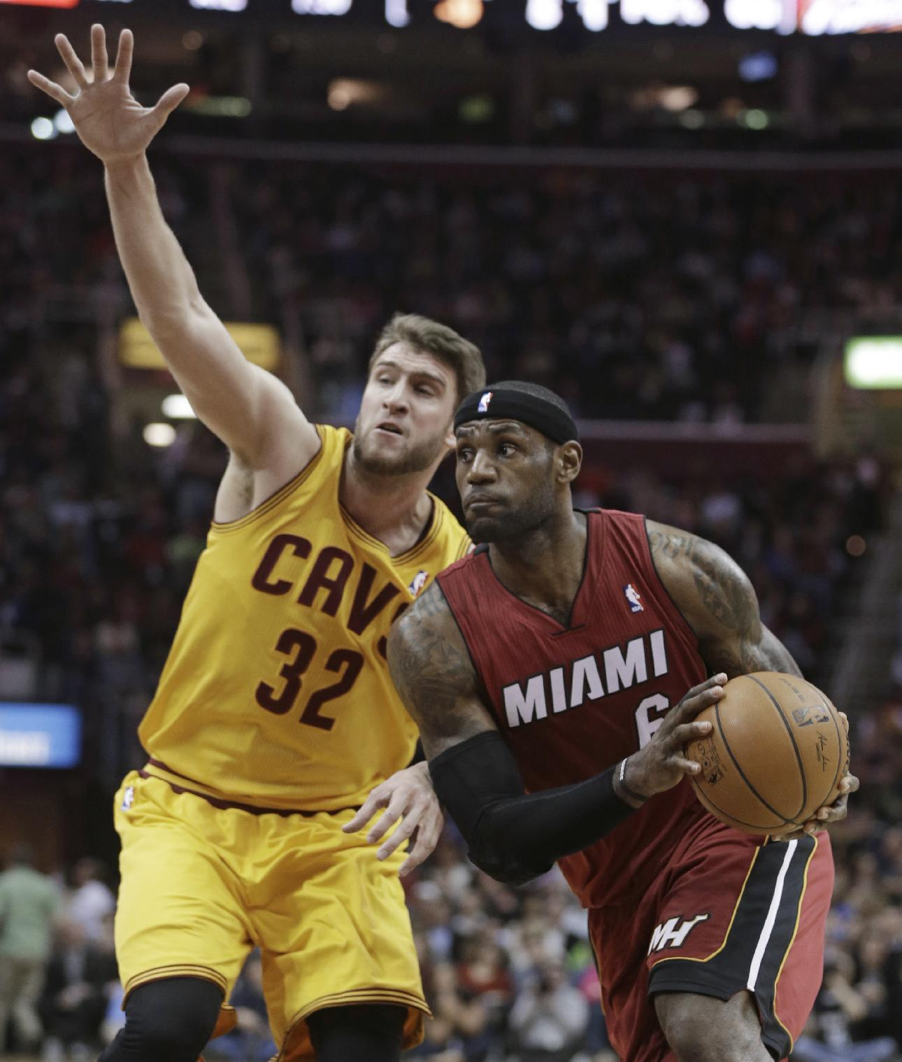 Miami Heat's LeBron James (6) drives around Cleveland Cavaliers' Spencer Hawes (32) during the first quarter of an NBA basketball game Tuesday, March 18, 2014, in Cleveland