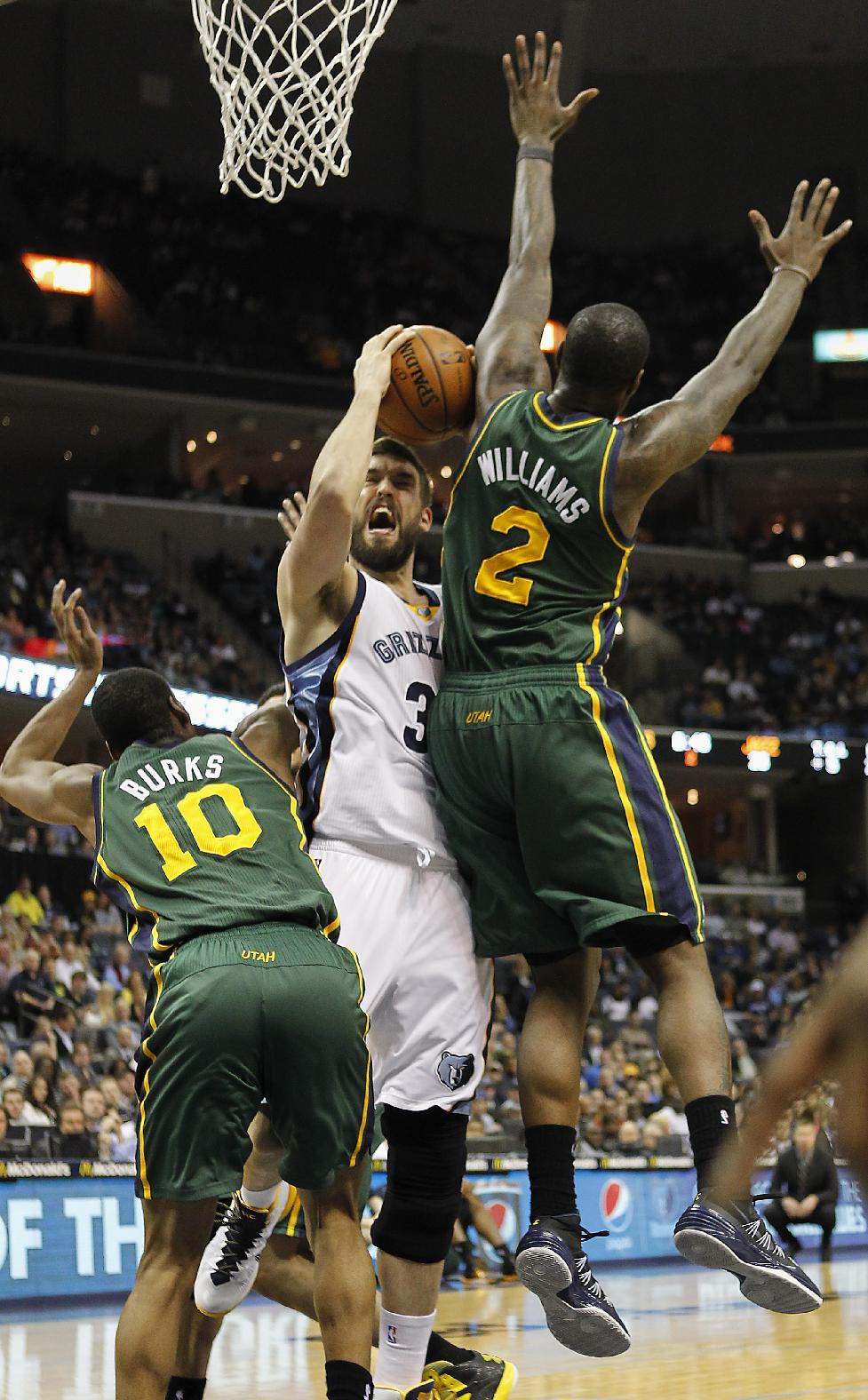 Memphis Grizzlies center Marc Gasol (33), of Spain, goes to the basket against Utah Jazz guard Alec Burks (10) and forward Marvin Williams (2) in the first half of an NBA basketball game on Wednesday, March 19, 2014, in Memphis, Tenn