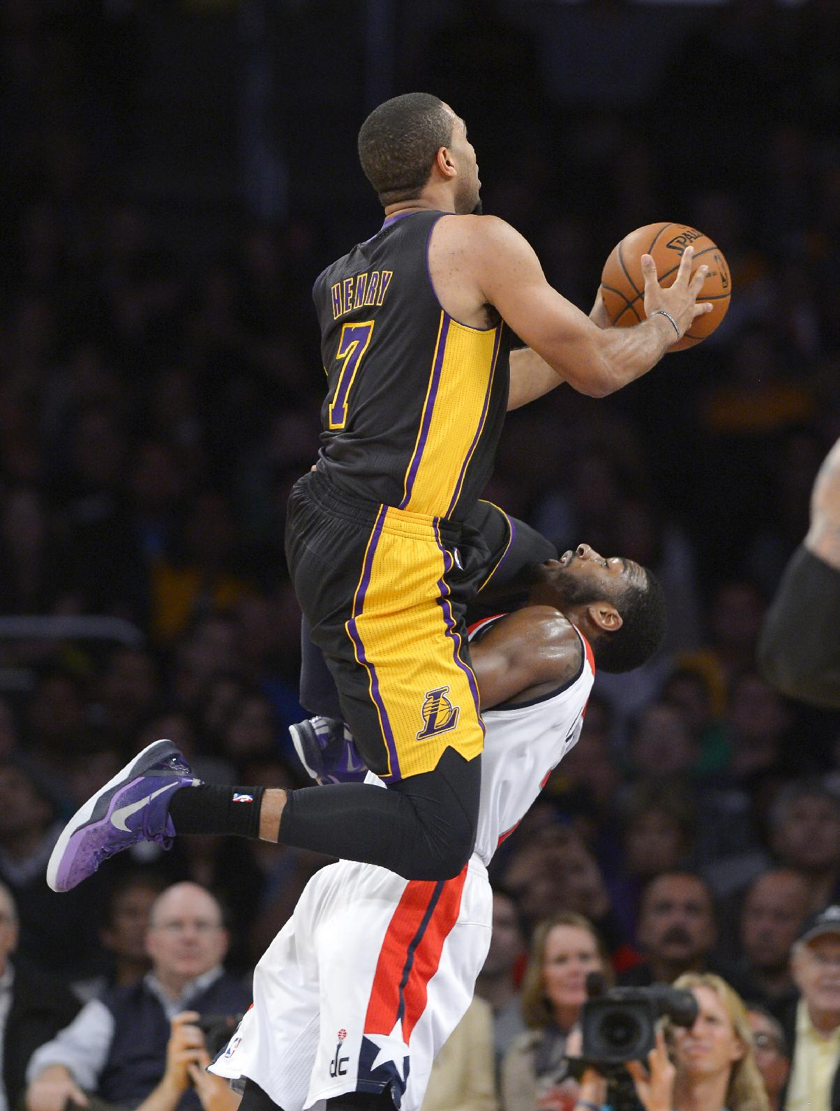 Los Angeles Lakers forward Xavier Henry, left, goes up for a shot as Washington Wizards guard John Wall defends during the second half of an NBA basketball game, Friday, March 21, 2014, in Los Angeles. The Wizards won 117-107