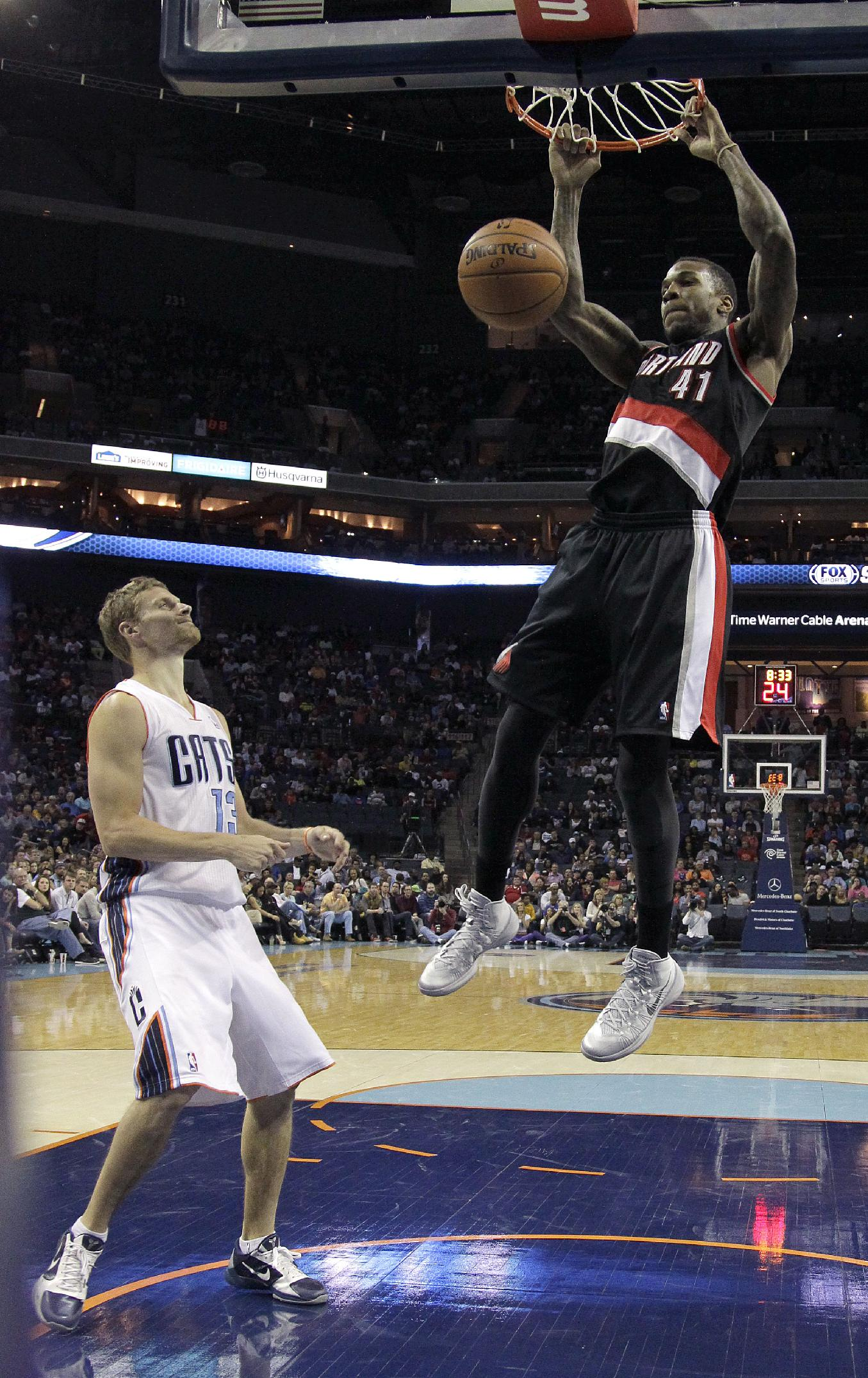 Charlotte Bobcats' Luke Ridnour (13) can only watch as Portland Trail Blazers' Thomas Robinson (41) dunks during the first half of an NBA basketball game in Charlotte, N.C., Saturday, March 22, 2014