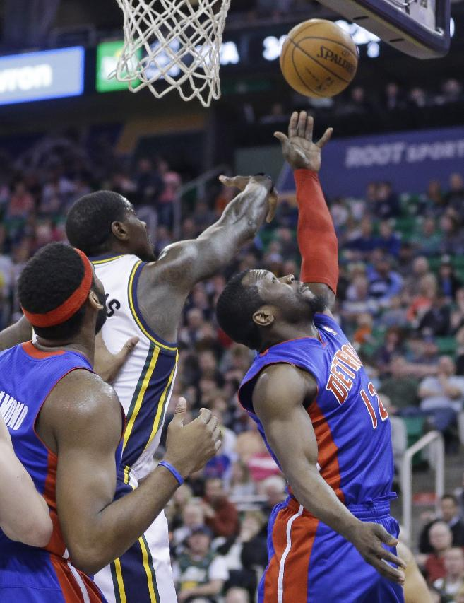 Detroit Pistons' Will Bynum (12) lays the ball up as Utah Jazz's Marvin Williams, center, defends while Detroit Pistons' Andre Drummond, left, looks on in the second quarter during an NBA basketball game Monday, March 24, 2014, in Salt Lake City