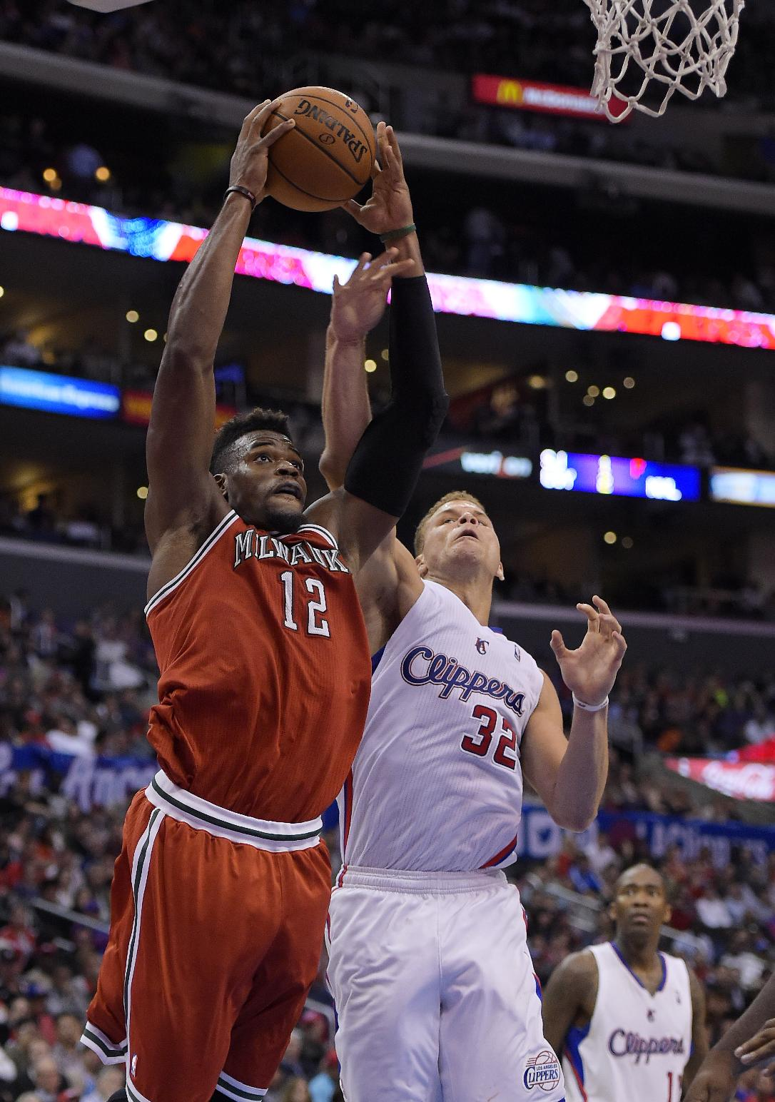 Milwaukee Bucks forward Jeff Adrien, left, goes up for a shot as Los Angeles Clippers forward Blake Griffin defends during the second half of an NBA basketball game, Monday, March 24, 2014, in Los Angeles. The Clippers won 106-98