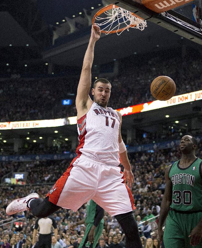 Toronto Raptors center Jonas Valanciunas (17) slams home a dunk against Boston Celtics forward Jeff Green (8) during first half NBA action in Toronto on Friday March 28, 2014