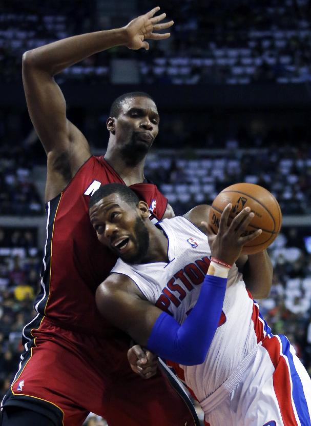 Detroit Pistons center Greg Monroe, bottom, moves to the basket against Miami Heat center Chris Bosh during the first half of an NBA basketball game on Friday, March 28, 2014, in Auburn Hills, Mich