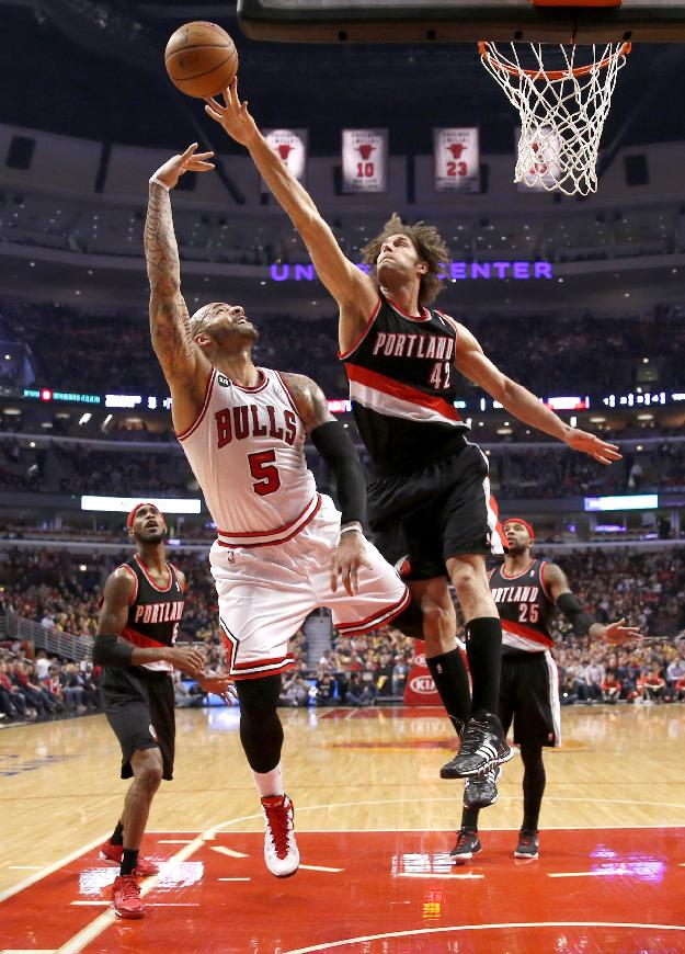Portland Trail Blazers center Robin Lopez (42) blocks the shot of Chicago Bulls forward Carlos Boozer (5) during the first half of an NBA basketball game Friday, March 28, 2014, in Chicago