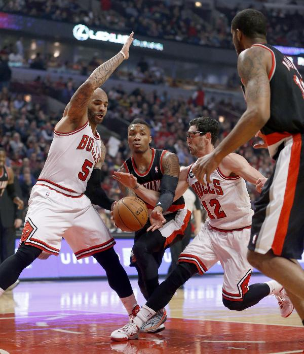 Portland Trail Blazers guard Damian Lillard, center, passes the ball to LaMarcus Aldridge, right as Chicago Bulls forward Carlos Boozer (5) and Kirk Hinrich (12) defend during the first half of an NBA basketball game Friday, March 28, 2014, in Chicago