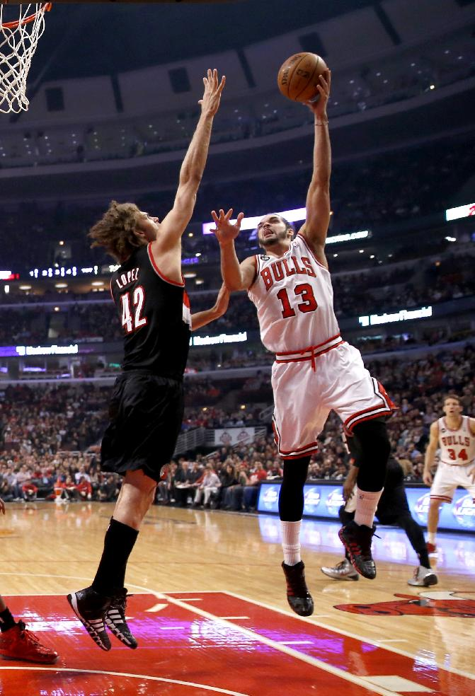 Chicago Bulls center Joakim Noah (13) shoots over Portland Trail Blazers center Robin Lopez (42) during the first half of an NBA basketball game Friday, March 28, 2014, in Chicago