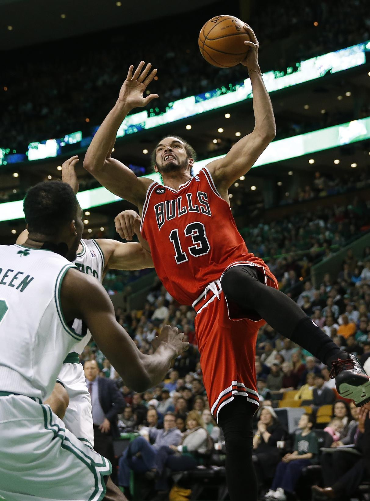 Chicago Bulls' Joakim Noah (13) goes up to shoot in front of Boston Celtics' Jeff Green in the first quarter of an NBA basketball game in Boston, Sunday, March 30, 2014