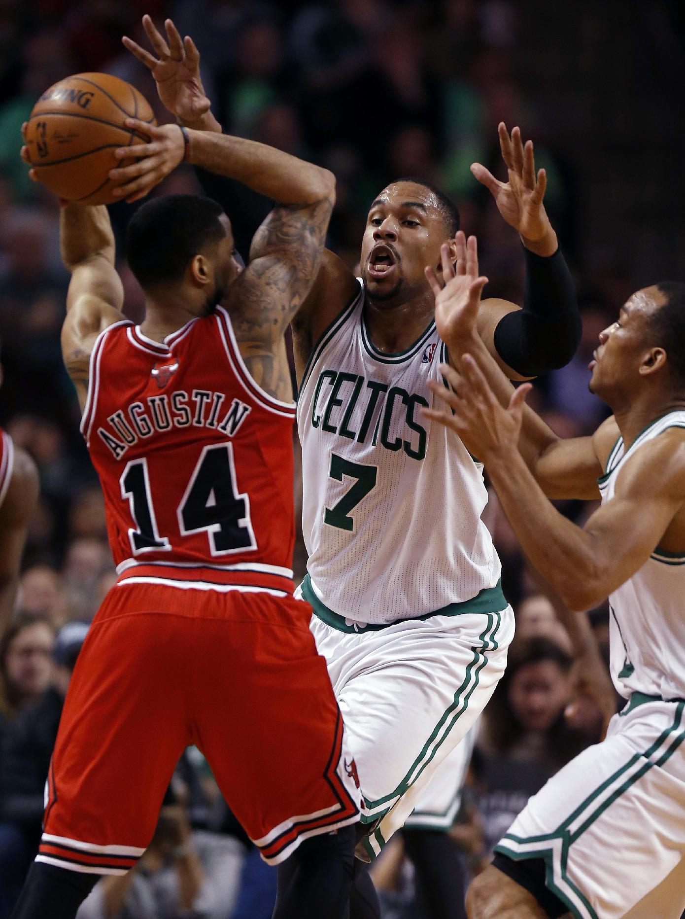 Boston Celtics' Jared Sullinger (7) defends against Chicago Bulls' D.J. Augustin (14) in the fourth quarter of an NBA basketball game in Boston, Sunday, March 30, 2014. The Bulls won 107-102