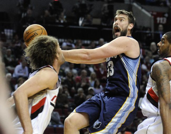 Memphis Grizzlies' Marc Gasol (33) shoots against Portland Trail Blazers' Robin Lopez, left, and LaMarcus Aldridge, right, during the first half of an NBA basketball game in Portland, Ore., Sunday March 30, 2014