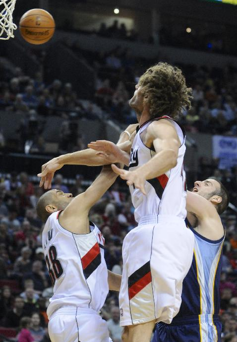 Memphis Grizzlies' Kosta Koufos (41) has his shot blocked by Portland Trail Blazers' Robin Lopez (42) with Nicolas Batum (88) during the first half of an NBA basketball game in Portland, Ore., Sunday March 30, 2014