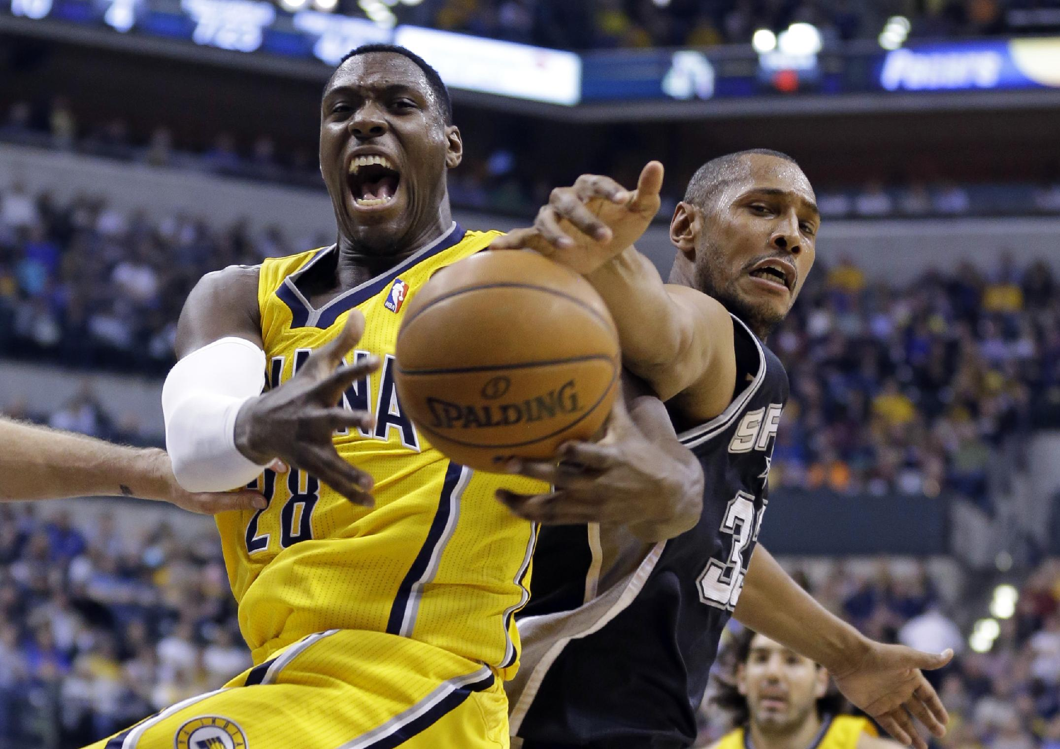 Indiana Pacers center Ian Mahinmi, left, and San Antonio Spurs forward Boris Diaw battle for rebound in the first half of an NBA basketball game in Indianapolis, Monday, March 31, 2014
