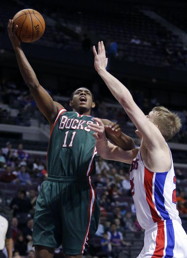 Milwaukee Bucks guard Brandon Knight (11) takes a shot against Detroit Pistons guard Kyle Singler during the first half of an NBA basketball game Monday, March 31, 2014, in Auburn Hills, Mich
