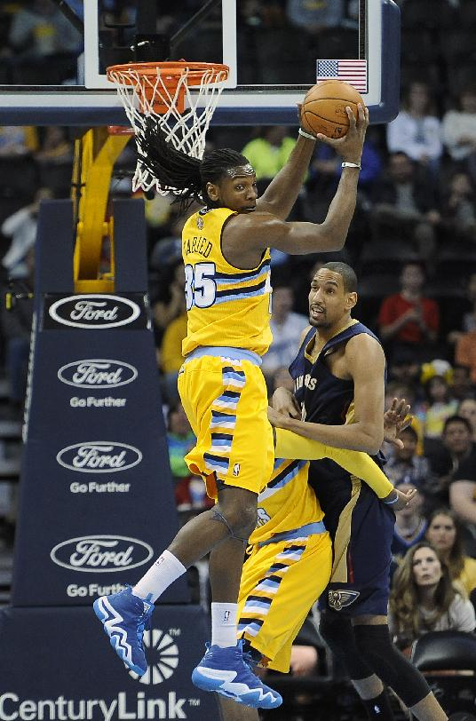 Denver Nuggets forward Kenneth Faried, left, grabs a rebound over New Orleans Pelicans center Alexis Ajinca, of France, right, in the first half of an NBA basketball game  on Wednesday, April 2, 2014, in Denver