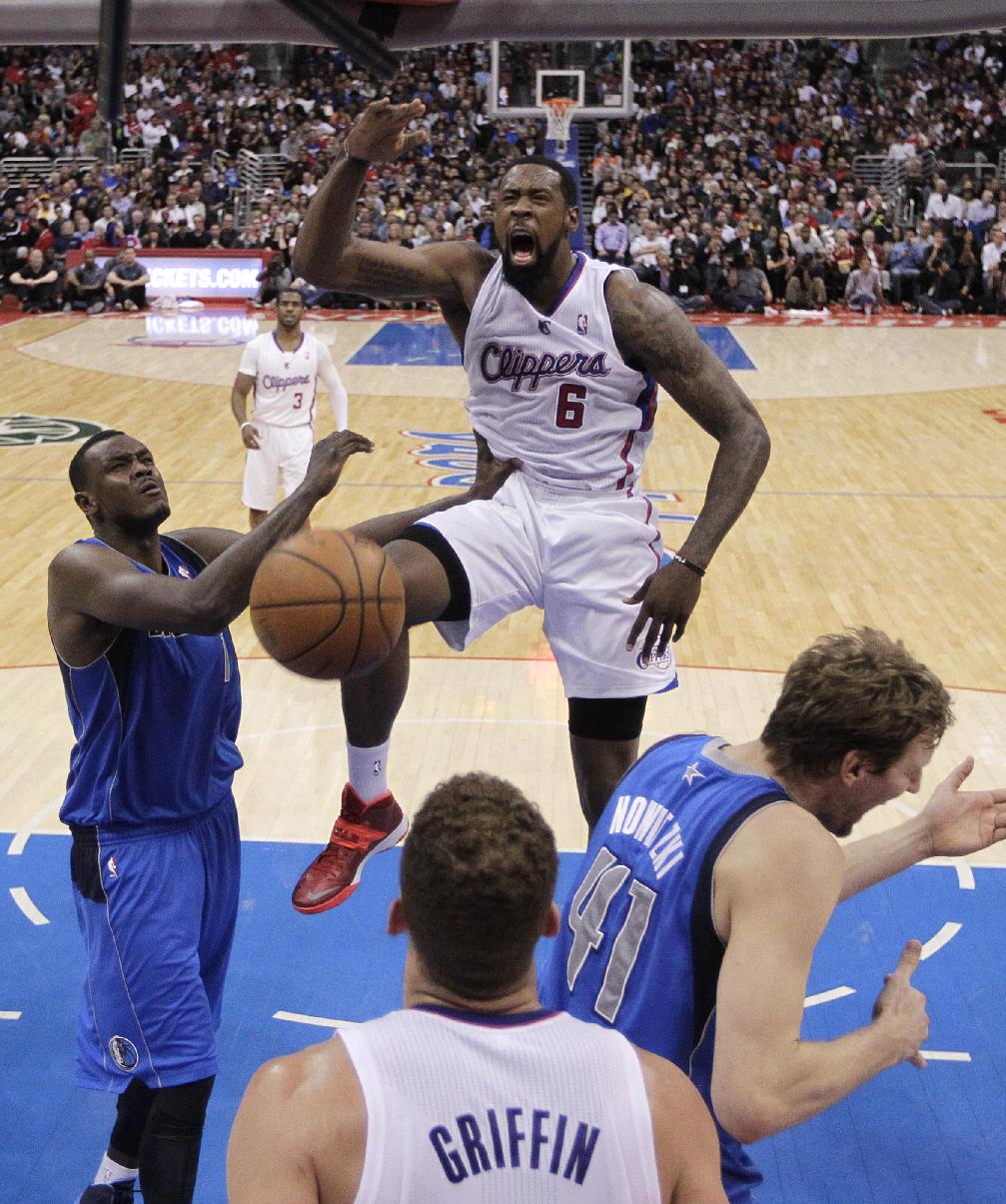 Los Angeles Clippers' DeAndre Jordan (6) dunks in front of Dallas Mavericks' Samuel Dalembert (1) and Dirk Nowitzki (41) during the first half of an NBA basketball game Thursday, April 3, 2014, in Los Angeles