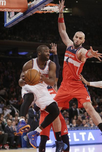 New York Knicks' Raymond Felton (2) passes away from Washington Wizards' Marcin Gortat (4) during the first half of an NBA basketball game Friday, April 4, 2014, in New York