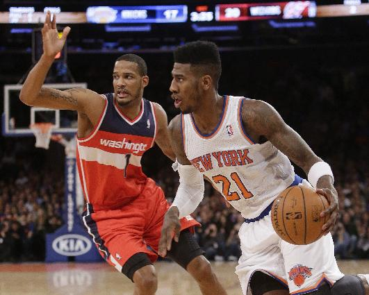 New York Knicks' Iman Shumpert (21) drives past Washington Wizards' Trevor Ariza (1) during the first half of an NBA basketball game Friday, April 4, 2014, in New York